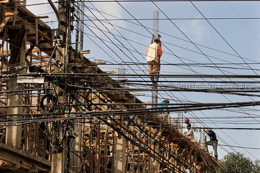 Burmese workers laboring at building site on December 20 of 2006 in Mae Sot, Thailand. Immigrants in Thailand do very hard jobs for much smaller fee than Thais would do..Burma has since 1962 been ruled by dictator Burman Regimes. Pro democrats and minority ethnics have since been object of human rights abuses and armed minority groups has appeared bringing a state of Civil War..This situation makes every days people to flee their villages to go to Thailand..Once in Thailand the illegal immigrants are very vulnerable as there is non law which support them. Although they are not allowed to work or do anything, the Thai industry uses them as cheap labour for cheaper production.
