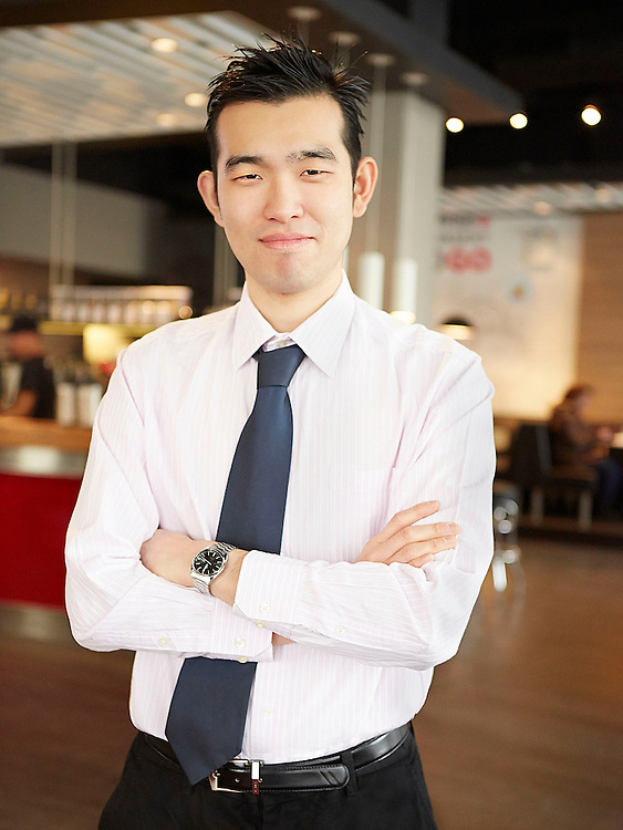 Portrait photograph of a confident Chinese businessman standing inside a cafe