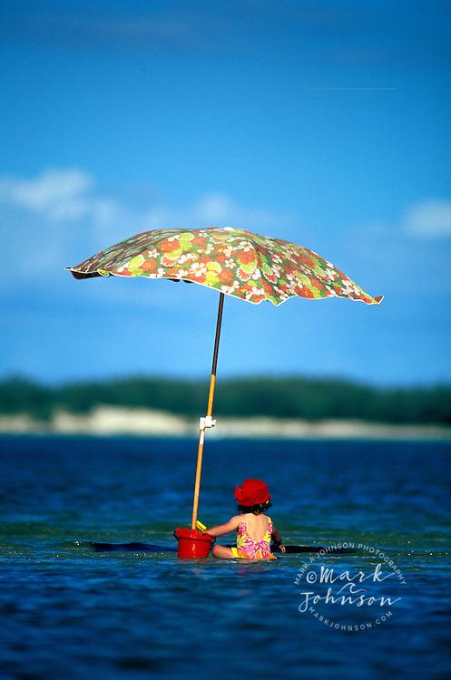 Australia, Queensland, Little girl at the beach under beach umbrella