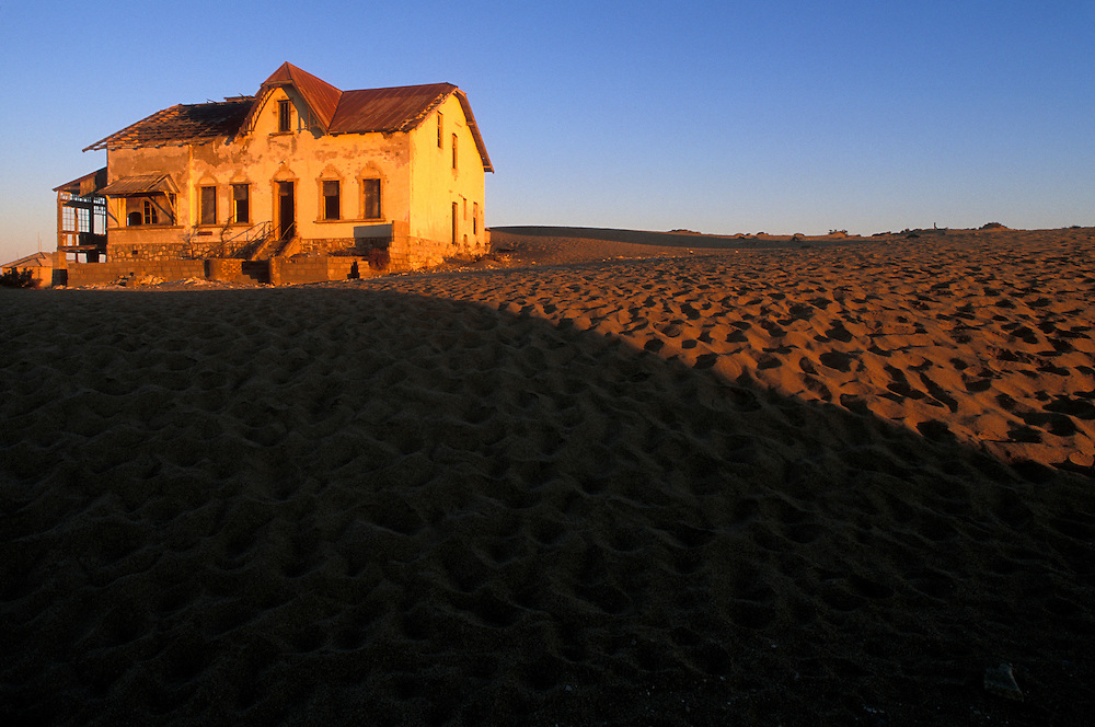 Africa, Namibia, Kolmanskop, Setting sun lights buildings at abandoned diamond mining ghost town near Lüderitz