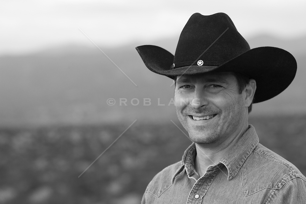 portrait of a sexy middle aged cowboy smiling