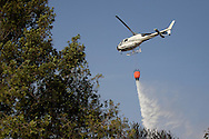 A firefighters' helicopter drop water to extinguish a forest fire in San Agustin de Guadalix on August 11, 2012, near Madrid, Spain. During a heat wave dozens of forest fires have appeared in Spain, three of them at National Parks, like Teide, Doñana or Cabañeros, and also thousands of people had to be evacuated at La Gomera and Tenerife, in the Canary Islands.