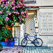 """Waiting"" by Asma Faisal.  A lonely blue bike leans up against the wall, waiting for his owner to return."