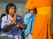 "02 JANUARY 2015 - KHLONG LUANG, PATHUM THANI, THAILAND: A woman prays at Wat Phra Dhammakaya as a monk walks past her at the start of the 4th annual Dhammachai Dhutanaga (a dhutanga is a ""wandering"" and translated as pilgrimage). More than 1,100 monks are participating in a 450 kilometer (280 miles) long pilgrimage, which is going through six provinces in central Thailand. The purpose of the pilgrimage is to pay homage to the Buddha, preserve Buddhist culture, welcome the new year, and ""develop virtuous Buddhist youth leaders."" Wat Phra Dhammakaya is the largest Buddhist temple in Thailand and the center of the Dhammakaya movement, a Buddhist sect founded in the 1970s.   PHOTO BY JACK KURTZ"