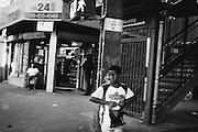 A boy crosses Broadway toward Bedford-Stuyvesant after stopping in a bodega in Bushwick, NY.