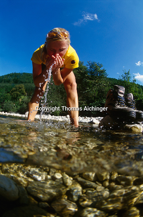 MR Young caucasian blonde woman refreshing herself in a mountain austrian river