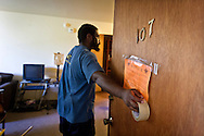 MILWAUKEE, WI — AUGUST 8, 2014: Harry Woods with Eagle Moving and Storage Company places a notice of tenant eviction on the door to an apartment at 714 West Galena Avenue in Milwaukee. The tenant was not present for the eviction.