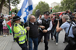Whitehall, London, September 9th 2015.  Police arrest an Israeli supporter following a scuffle as pro Palestinian and Israeli counter-protesters clash in Whitehall as the Palestinian Solidarity campaign demands the arrest of Israel's PM Benyamin Netanyahu for war crimes in the 2014 war with Palestinians in Gaza.  // Contact: paul@pauldaveycreative.co.uk Mobile 07966 016 296