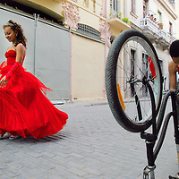 """A girl preparing to celebrate her quinceañera, or """"sweet 15"""" birthday, passes by a boy fixing his bicycle in Old Havana."""
