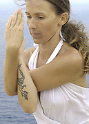 Model Released: Attractive young woman, artist Lena Tancredi, practicing yoga in front of the Mediterranean Sea, Ibiza, Spain - Photo by Nano Calvo