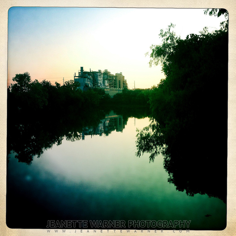Holly Power Plant in Austin, TX, reflects back into the water on a calm night from the hike and bike trail.