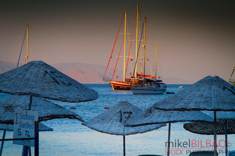 Beach and sailboat. Datca city.<br /> Datca peninsula, Mugla province, Anatolia, Turkey.