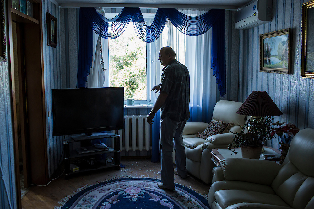 A man shows damage to his apartment after the building was hit by a suspected grad rocket strike on Tuesday, July 29, 2014 in Donetsk, Ukraine.
