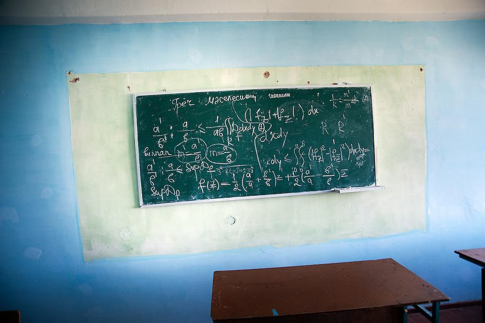 An abandoned chalkboard in an empty classroom.