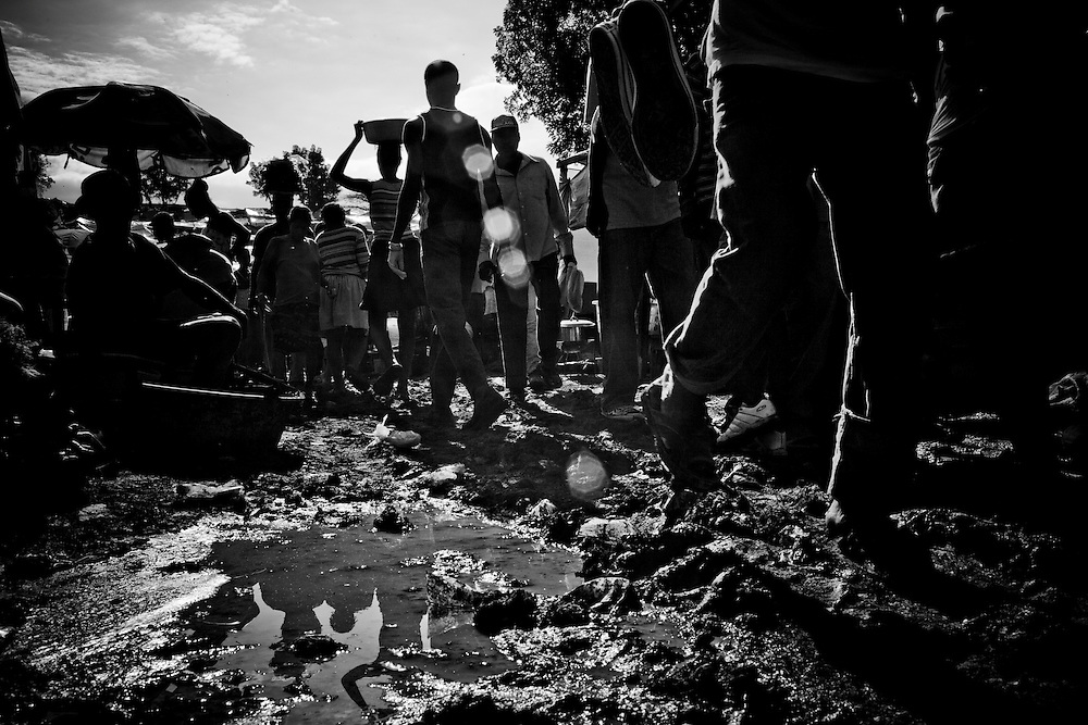 Residents of a camp for those displaced by the recent earthquake walk through thick mud after rain overnight in Petionville, outside Port-au-Prince, Haiti.