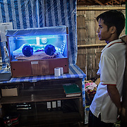 An ethnic Karen father looks on at his newborn child at makeshift neo-natal unit inside the Mae Hla refugee camp along the Thai-Burma border.  More than 100,000 ethnic Karen from Burma are living in refugee camps in Thailand today.