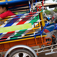 A tuk tuk driver awaits a fare in the busy Lao capital.