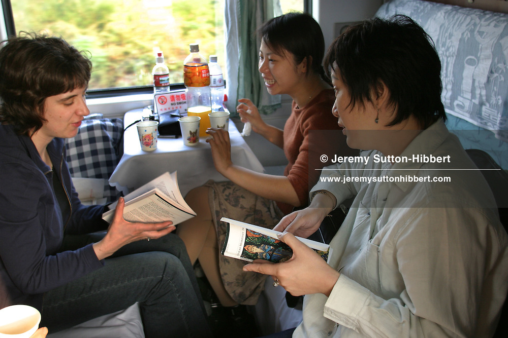 Sinead Morrissey (on left) -a Northern Irish poet from Belfast, talks with Jade River-translator (centre) and Chinese writer Zhang Mei (on right, white shirt) as she travels on the 30 hour train trip between Kunming and Guangzhou as part of the Think UK Writers Train project. The Think UK China Writers Train is a project, in collaboration with the British Council, to take 4 UK writers/poets and 4 Chinese writers/poets around China by train visiting 6 major cities, in 17 days, to hold talks, seminars and readings of their work.