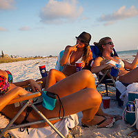 Bikini-clad, sun worshippers relax with beer and books along St. Pete Beach.