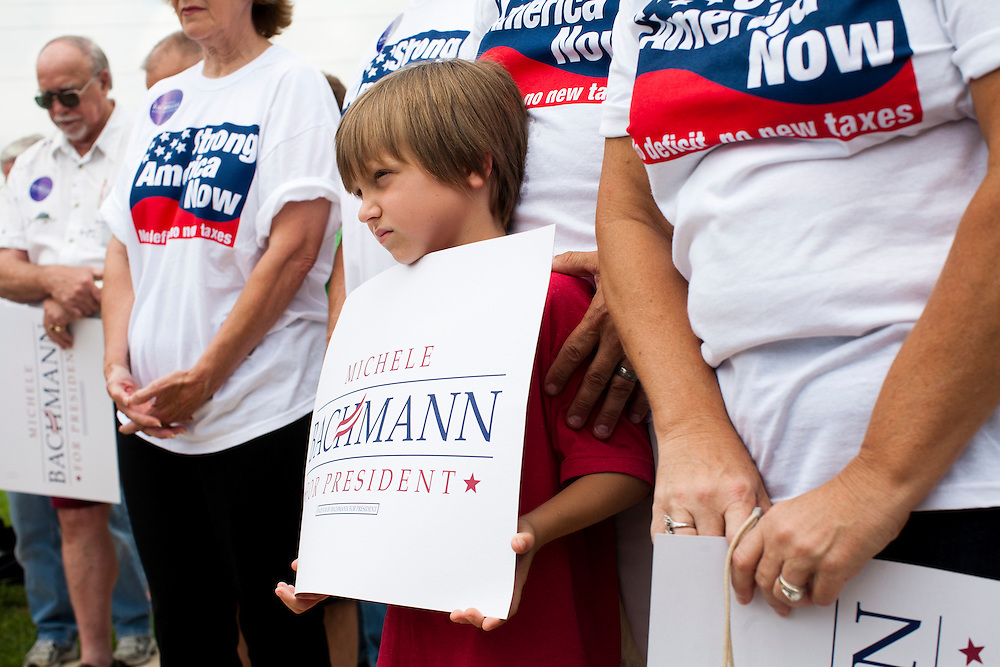 A boy listens to Republican presidential hopeful Michele Bachmann during a campaign stop on Saturday, August 6, 2011 in Cedar Rapids, IA.