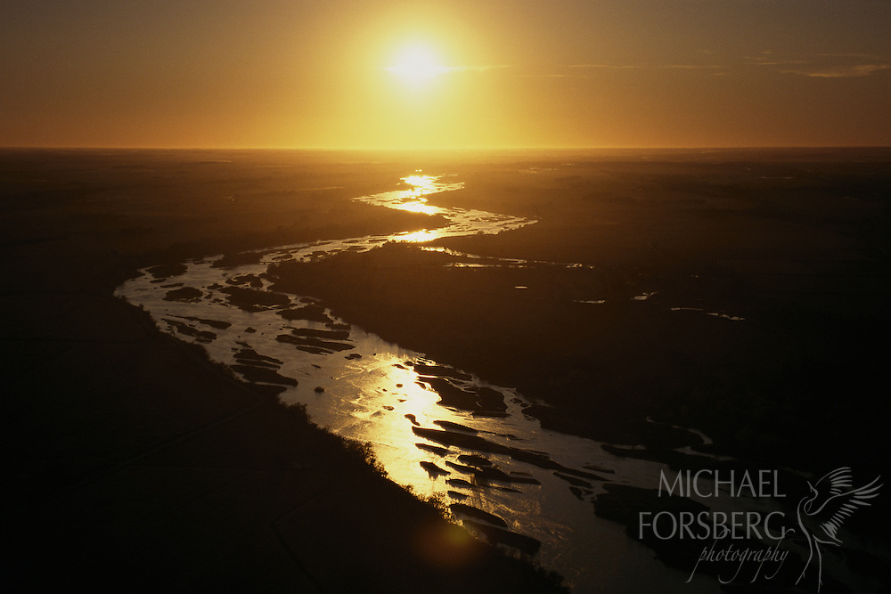 Platte River, Central Nebraska. The sun sets over the braided streams that form the Platte River. Located in the western United States, the Platte River is over 300 miles in length and drains a large portion of the central Great Plains in Nebraska and the eastern Rocky Mountains in Colorado and Wyoming. It serves as a tributary to the Missouri River, which in turn is a tributary to the Mississippi River. The Platte River is in the middle of the Central Flyway, a primary North-South Corridor for millions of migratory birds. The 80-mile stretch of the river known as Big Bend Reach and it's adjacent wet meadows provide a crucial stopover location for over 500,000 sandhill cranes, millions of ducks and geese and endangered species including the Whopping Crane, Piping Plover, and Interior Least Tern.