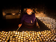 16 MARCH 2017 - KATHMANDU, NEPAL: A woman lights butter lamps at a Tibetan Buddhist monastery next to Boudhanath Stupa in Kathmandu. Boudhanath Stupa is the holiest site in Nepali Buddhism. It is also the center of the Tibetan exile community in Kathmandu. The Stupa was badly damaged in the 2015 earthquake but was one of the first buildings renovated.      PHOTO BY JACK KURTZ