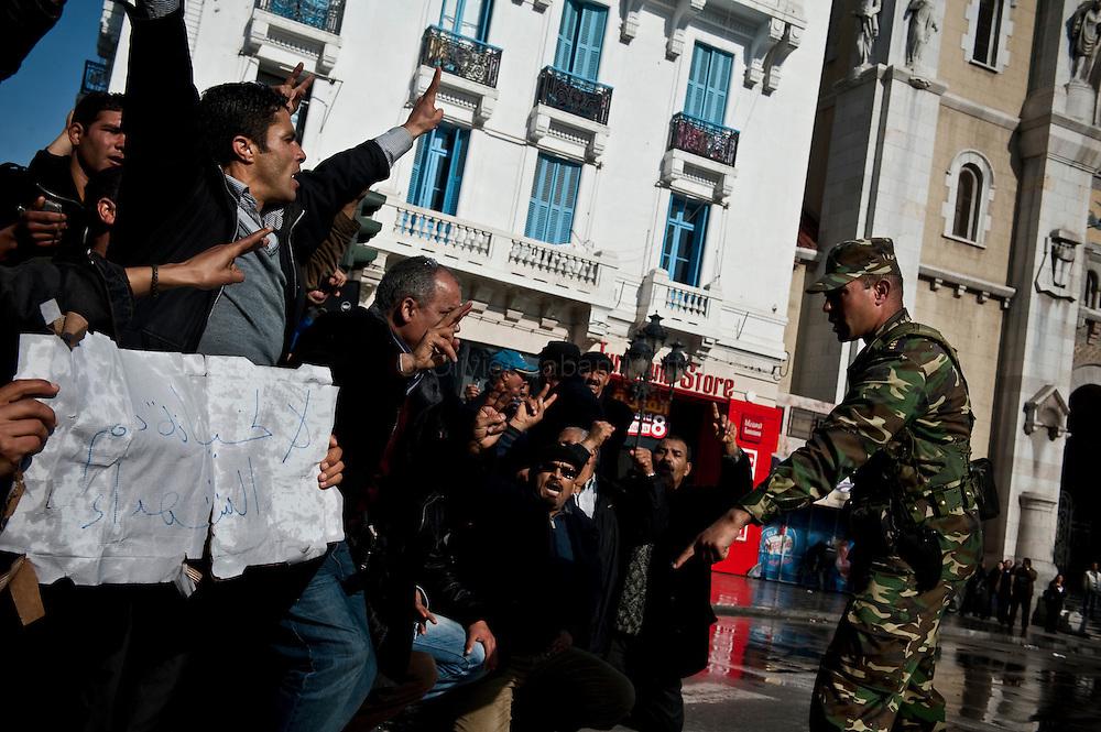 """Un militaire tente de contenir la marche d'opposants au régime de Ben Ali, le 17 janvier 2011 sur l'avenue Bourguiba à Tunis, venus protester contre la formation du nouveau gouvernement provisoire et réclamer """"le déracinement du système Ben Ali""""."""