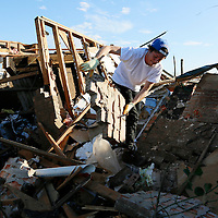 Josh Sallee throws a piece of a brick wall from a tornado-destroyed home on Heather Lane in Moore, Oklahoma May 21, 2013. A massive tornado tore through a suburb of Oklahoma City, wiping out whole blocks and killing at least 24.   REUTERS/Rick Wilking (UNITED STATES)
