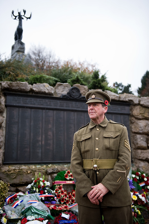 A man dressed with a Canadian Expeditionary Force  officers uniform standing in front of the Beaumont-Hamel Newfoundland Memorial.  The memorial is dedicated to the commemoration of the Newfoundland Regiment that fought in the battle of Somme and WWI in general. Most of the  Newfoundland Regiment were dead within 15 to 20 minutes of leaving their trench in the morning of the 1st July 1916 during the first day of the Battle of the Somme.