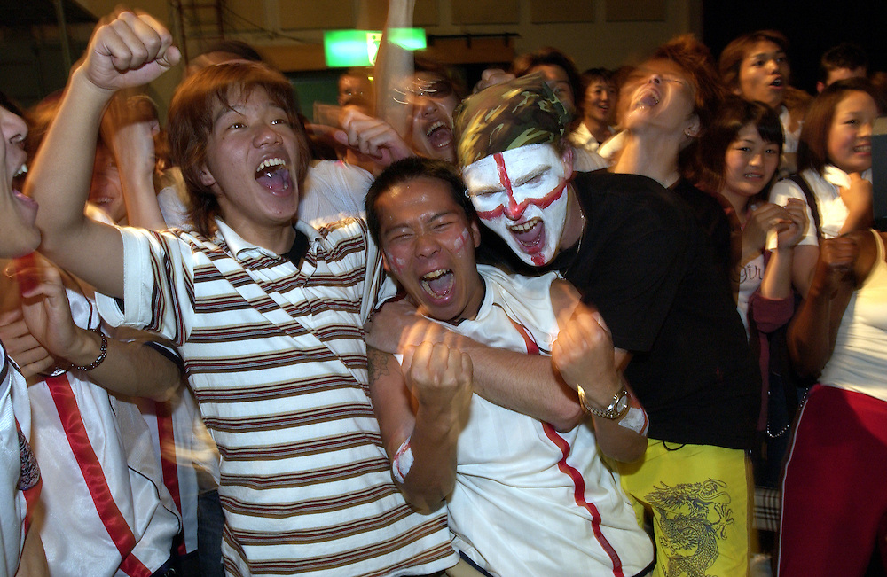 English soccer supporters and sympathetic Japanese fans celebrate England's 3 to 0 win against Denmark at the indoor screening of the England vs Denmark World Cup match 15/06/02 Niigata Japan..©David Dare Parker/AsiaWorks Photography
