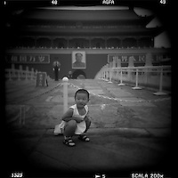 Asia, China, Beijing, Blurred black and white image of young child posing for snapshots at Gate of Heavenly Peace in the Forbidden City on summer afternoon