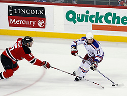 February 1, 2008; Newark, NJ, USA; New York Rangers center Brandon Dubinsky (17) avoids a poke check from New Jersey Devils defenseman Colin White (5) during the third period at the Prudential Center in Newark, NJ.  The Rangers defeated the Devils 3-1.