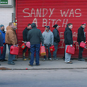 Watched over by Police, residents of Far Rockaway, Queens line up for gas. The Rockaways area of New York City was badly damaged by Hurricane Sandy.