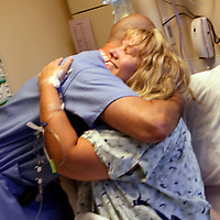 Bariatric surgery patient Carolyn Dawson (R) gets a final hug from her surgeon Dr. Michael Snyder (L) just before Dawson underwent laparoscopic gastric bypass at Rose Medical Center in Denver August 30, 2010 performed by Snyder. Dawson hoped to lose almost 150 pounds with the help of the procedure. REUTERS/Rick Wilking (UNITED STATES)