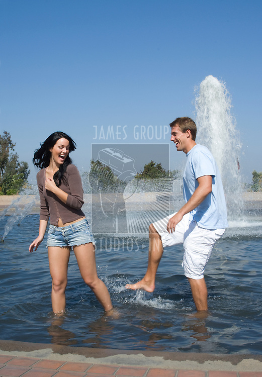 Young couple splashing water in a public fountain on a clear day