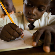 Boy drawing in exercise book during class at the Ying Anglican Primary School in the Savelugu-Nanton district, northern Ghana on Monday June 4, 2007.
