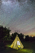 A modern tipi at the Two Trees/Riverwalk picnic site at Grasslands National Park, Saskatchewan, August 25, 2014, under the stars of the Big Dipper above the trees. This is a single 60-second exposure at f/2.8 and ISO 4000 with the Canon 6D and 14mm Rokinon lens. I provided the interior illumination to the tipi.