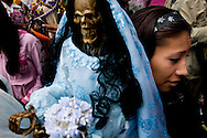 A Sante Muerte devotee carries her Sante Muerte figure to be blessed at a popular shrine in Tipito in Mexico City.