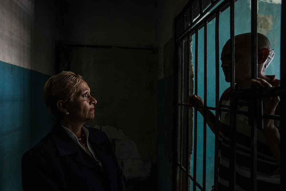 BARQUISIMETO, VENEZUELA - JULY 28, 2016: Schizophrenic patient, Emeregildo Aranguren, pleads with head nurse, &Eacute;vila Garc&iacute;a<br /> to let him out of solitary confinement.  Aranguren stabbed and murdered his stepfather in 2006, before being diagnosed with schizophrenia and treated with psychiatric drugs. He does not have two of the medicines that he needs to keep him stable, and has been growing increasingly anxious.  Hospital staff put him in isolation because they fear that without his medicine, he can become violent again. When he is medicated, Mr. Aranguren is much more composed and happier. He is able to participate in group therapy and art projects, like making intricate hammocks by hand&hellip;but without his medications, he is considered to dangerous to mix with the rest of patients. The economic crisis that has left Venezuela with little hard currency has also severely affected its public health system, crippling hospitals like El Pampero Psychiatric Hospital by leaving it without the resources it needs to take care of patients living there, the majority of whom could live much more fulfilling lives if they had the medicines that they need. The hospital has not employed a psychiatrist for over two years. Drugs used to combat bipolar disorder, epilepsy, schizoaffective disorder and chronic anxiety are now in short supply, as are numerous sedatives and tranquilizers needed to care for patients. Members of the nursing staff debate daily which patients are the most unstable, to decide which patients will receive pills and which will go without. When a patient loses control, often the only thing they can do is lock them in an isolation cell to prevent them from hurting themselves, other patients and members of the staff.  PHOTO: Meridith Kohut