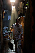 A man walks to work through the maze of alley ways in Dharavi, the slum made famous by the film 'Slumdog millionaire' - 2007