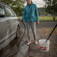"Bar tender Kaitlin Jones washes her friend's car in front of her home in Calistoga.  ""I love the pace of Calistoga...I grew up in a small town and this feels like home to me."""