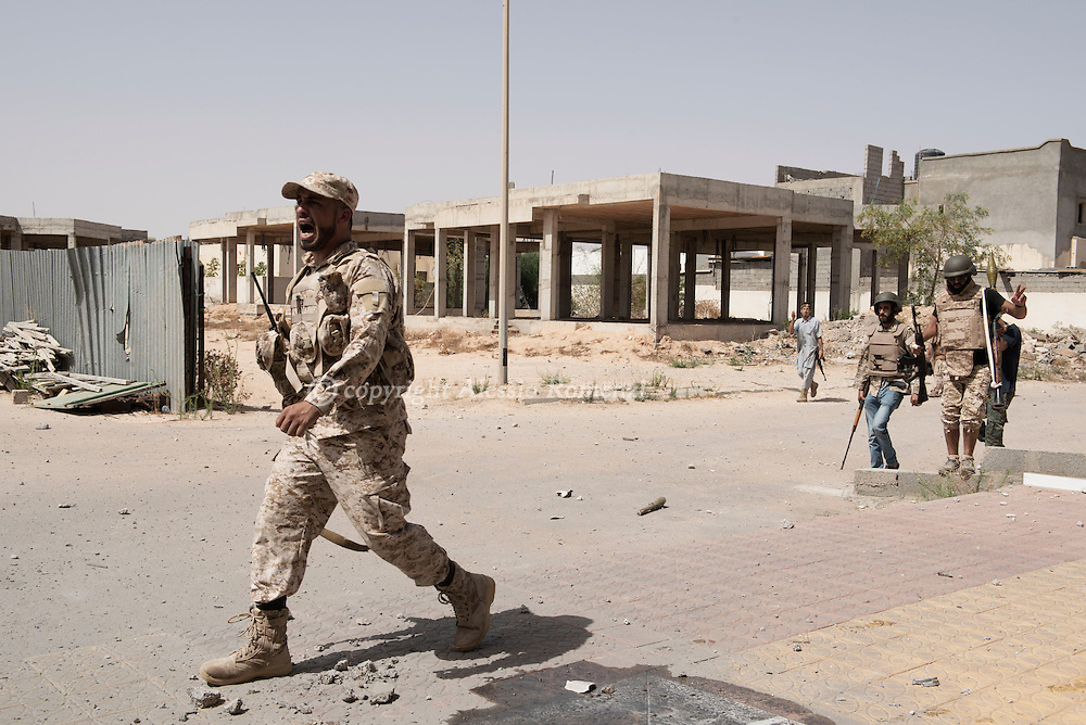 """Libya: Fighters affiliated with Libya's Government of National Accord's (GNA) shout """"Allah u akbar"""" (Allah is great"""" as they advance in 700 neighbourhood in Sirte. Alessio Romenzi"""