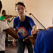 Instructor Aline Batard helps violin students learn finger placement.