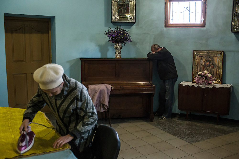 A woman irons a tablecloth in the basement of Saint Pokrovsky Church on Thursday, October 16, 2014 in Donetsk, Ukraine. Photo by Brendan Hoffman, Freelance