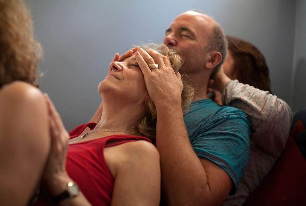 Thomas Stout, second from right, a licensed masseuse, rubs the head of host Candessa Hadsall, a certified Cuddle Party facilitator, at a home party in Minneapolis January 9, 2015.