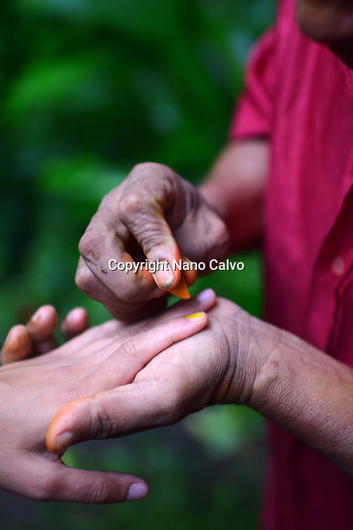 Catato López, Bribri man painting woman´s nails with natural made polish. A day with the Bribri, indigenous people in Limón Province of Costa Rica