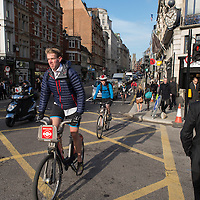 Young City workers cycling to work, London.