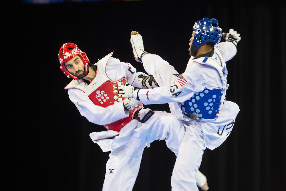 Maxine Potvin (L) of Canada tries to avoid a kick by Terrence Jennings of the United States during their semifinal contest in the men's -68kg weight class of Taekwondo at the 2015 Pan American Games in Toronto, Canada, July 20,  2015.  AFP PHOTO/GEOFF ROBINS
