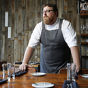 SHOT 8/15/13 4:13:03 PM - Justin Brunson, Owner and Executive Chef at Old Major restaurant in Denver, Co. Includes images of menu items : The Nose to Tail Plate : confit rib, pork chop, crispy belly, city ham, crispy ear, Denver Bacon Co. barbecue beans, cole slaw and corn bread $29 and Pan Seared Scallops : baby vegetables, fregola, spinach purée, toasted pine nuts, roasted garlic vinaigrette $27. The restaurant focuses on heritage-raised meats from Colorado farms, features an in-house butchery program and bills itself as contemporary farmhouse cuisine. (Photo by Marc Piscotty / © 2013)