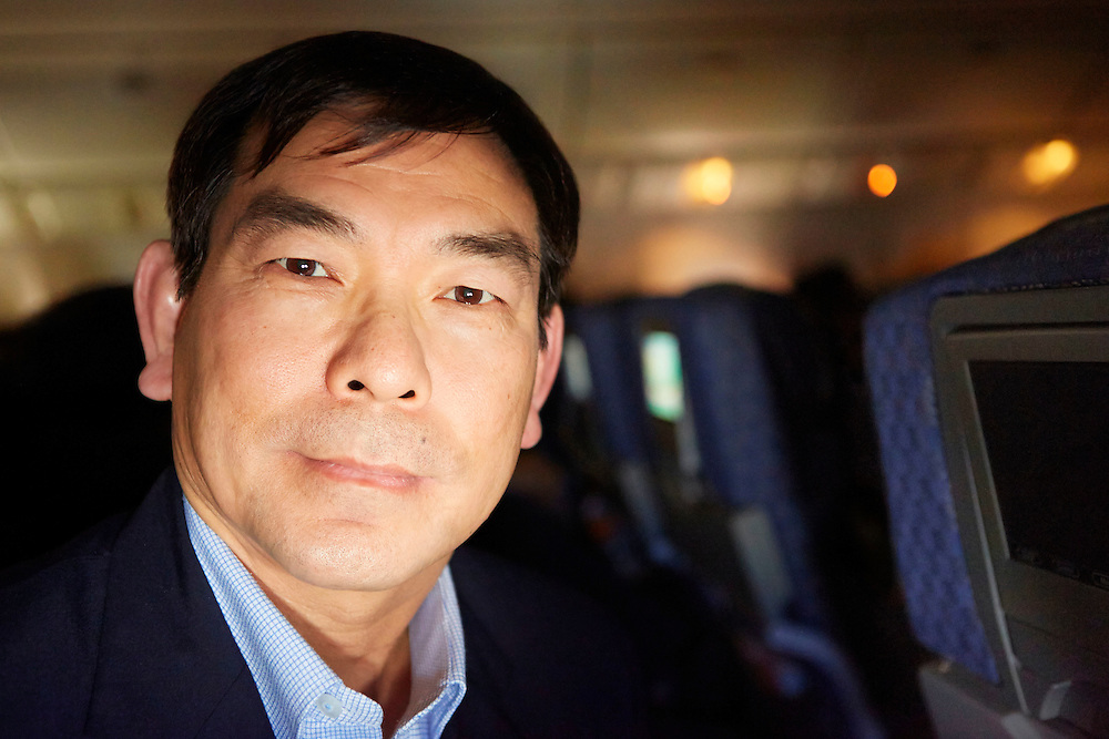 Portrait photograph of a Vietnamese traveler midflight on an international American Airlines flight from Dallas to Tokyo